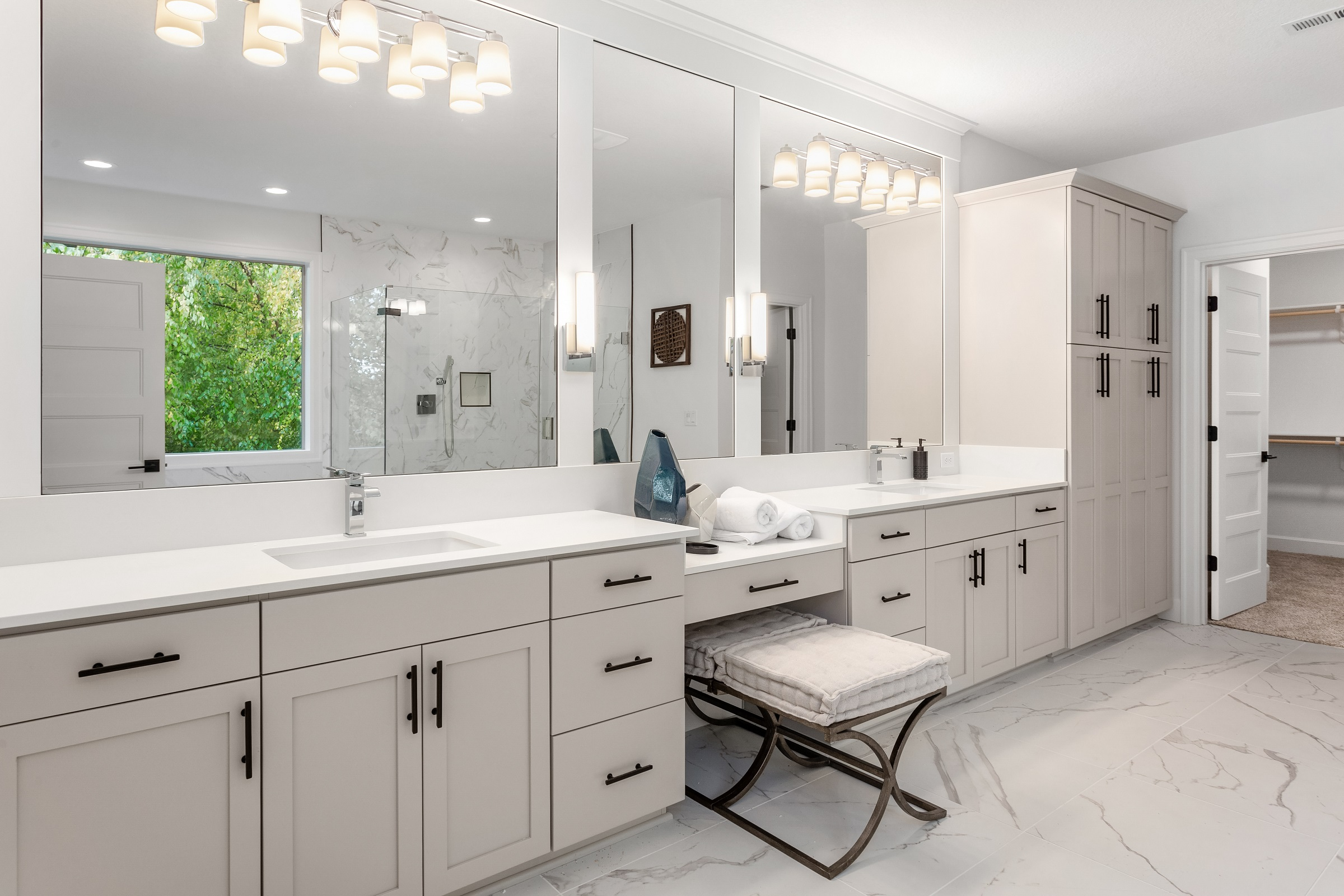 Bathroom in luxury home with double vanity, two mirrors, two sinks, and tile floor